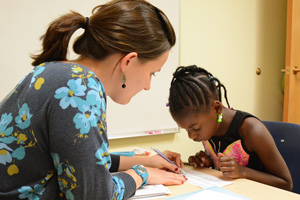 girl writing with occupational therapist