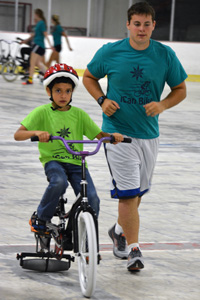 boy on bike with spotter alongside